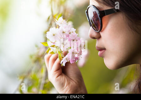 Young woman with blindfolded eyes feel out and smell a twig of cherry blossoms - Stock Photo