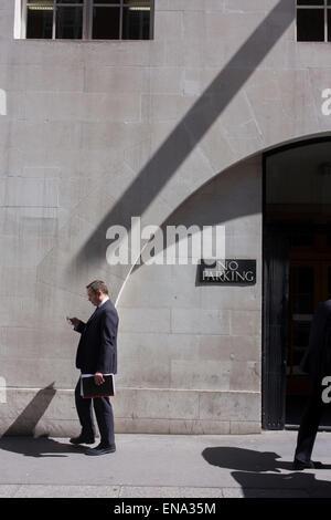 Businessman walks under diagonal shadow on a wall, off Fleet Street in the City of London. - Stock Photo