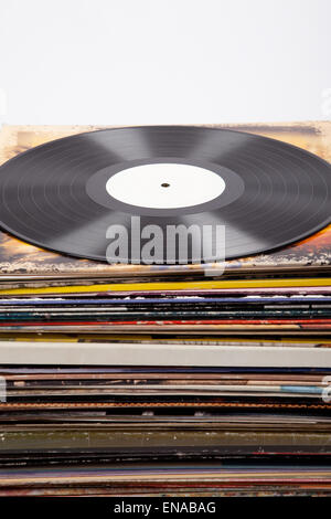 vinyl lp record with white label on a tower of album covers, retro, vintage, white background, - Stock Photo