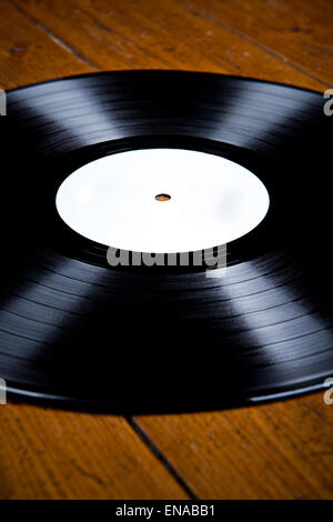 vinyl lp record with white label on wooden floor, light reflections, aerial view, - Stock Photo