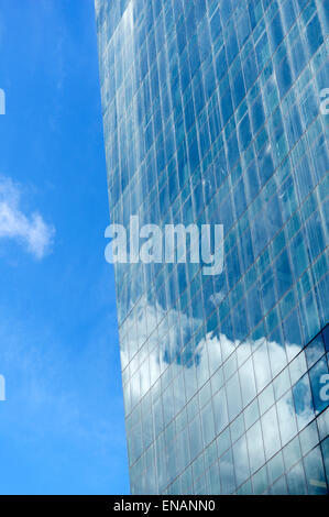 Clouds and blue sky reflected in the glass facade of an office tower in downtown Vancouver, BC, Canada - Stock Photo