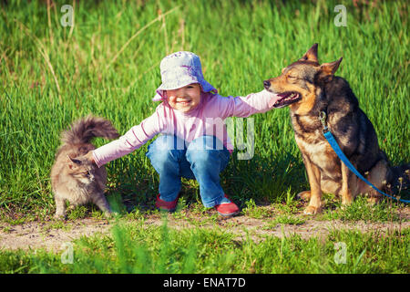 Happy little girl playing with dog and cat outdoors - Stock Photo