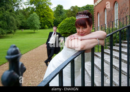 The bride and groom on the steps of Clandon Park - Stock Photo
