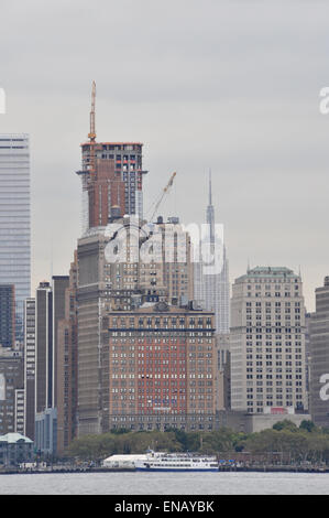 The Empire State building seen through New York towers from the river - Stock Photo