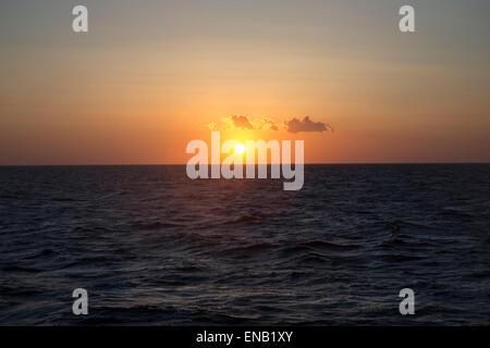 The sun setting over the Mediterranean sea as seen from a cruise ship - Stock Photo