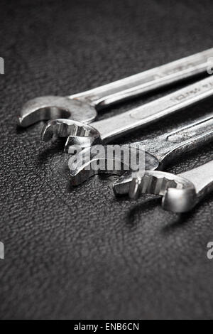 A selection of spanners on a black surface - Stock Photo