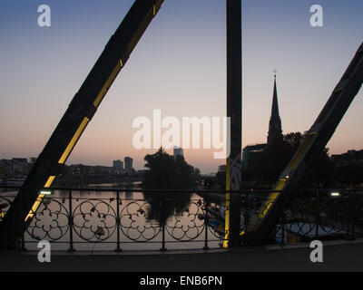 Eiserner Steg Bridge and business buildings in the center of Frankfurt, Germany, at sunrise - Stock Photo