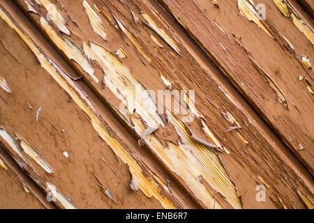 Old paint peeling from door revealing wood underneath - Stock Photo
