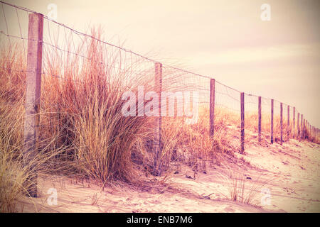 Vintage retro filtered photo of fence on a dune, nature background. - Stock Photo