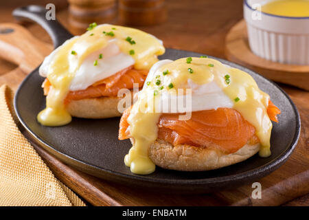 A delicious eggs benedict with smoked salmon, hollandaise sauce, and chives. - Stock Photo