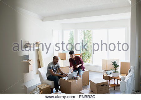 Couple at laptop surrounded by moving boxes - Stock Photo