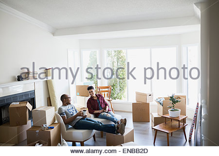 Couple surrounded by moving boxes relaxing with coffee - Stock Photo