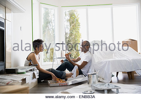 Couple taking a break from painting eating pizza - Stock Photo