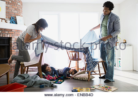 Parents creating fort over sleeping children - Stock Photo