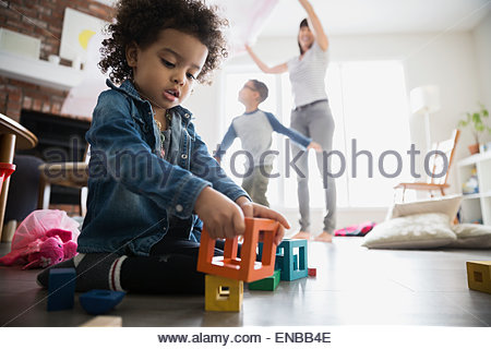 Girl playing with blocks on living room floor - Stock Photo