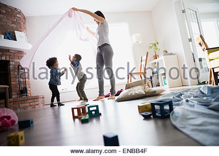 Children dancing under mother with sheet - Stock Photo