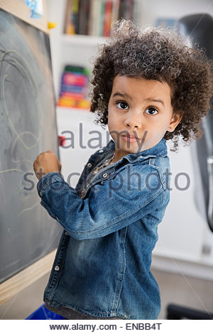 Girl with curly hair drawing at blackboard - Stock Photo