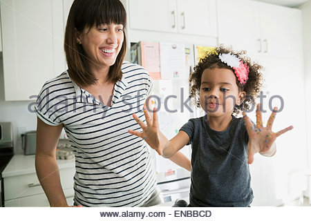 Mother watching daughter show messy baking hands - Stock Photo