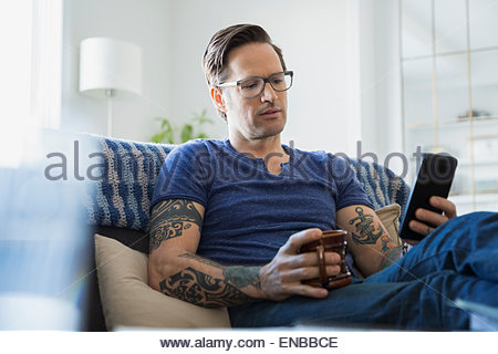 Man tattoos and coffee texting in living room - Stock Photo