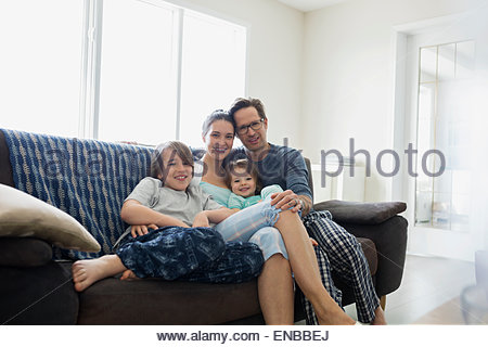 Portrait of smiling family in pajamas relaxing sofa - Stock Photo