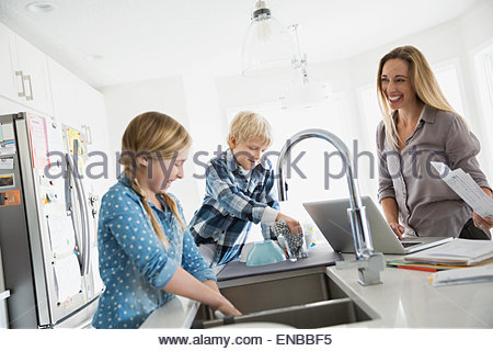 Mother at laptop watching children doing dishes - Stock Photo