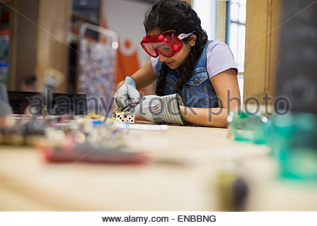 Girl wearing goggles assembling electronics at science center - Stock Photo