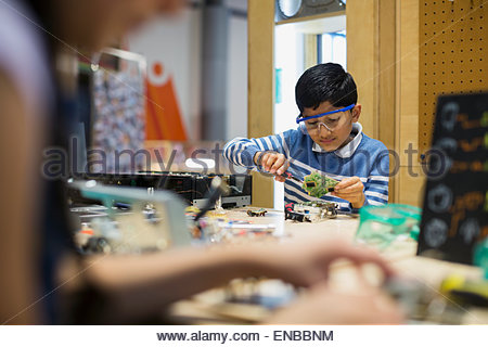 Boy wearing goggles assembling electronics at science center - Stock Photo