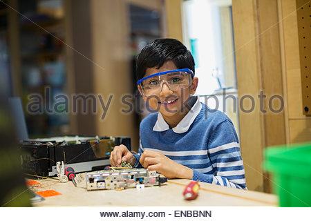 Portrait of smiling boy assembling electronics science center - Stock Photo