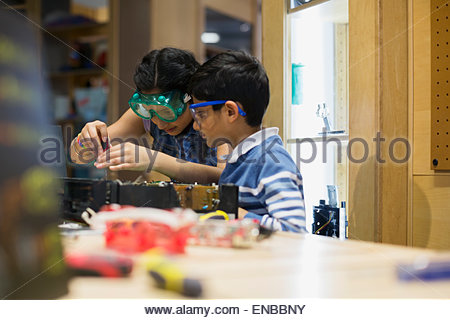Brother and sister assembling electronics at science center - Stock Photo