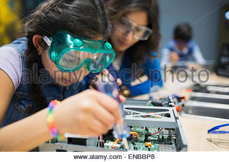 Mother watching daughter assembling electronics at science center - Stock Photo