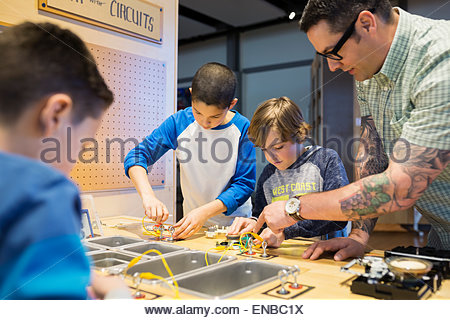 Teacher and students assembling electronic circuits science center - Stock Photo