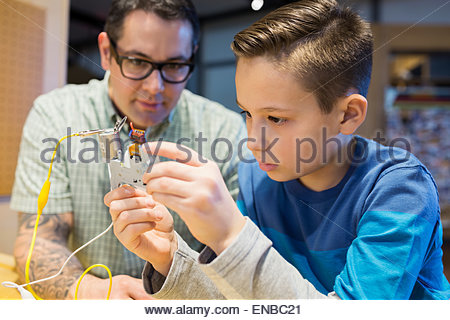 Teacher and student assembling electronic circuit science center - Stock Photo