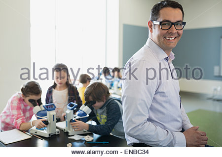 Portrait of confident science teacher in classroom laboratory - Stock Photo