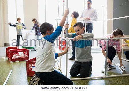 Students assembling model pipeline in science center - Stock Photo