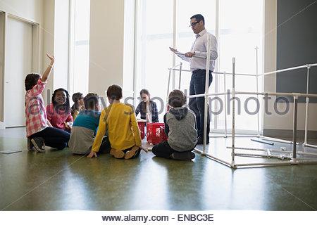Teacher guiding students on assembling model pipeline - Stock Photo