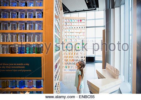 Curious girl looking up jar display science center - Stock Photo