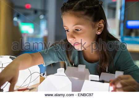 Curious girl playing at electricity grid science center - Stock Photo