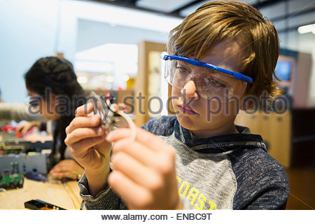 Curious boy assembling electronic circuit at science center - Stock Photo
