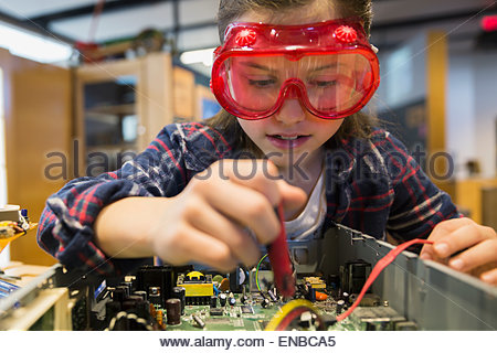Girl goggles assembling electronics circuit at science center - Stock Photo