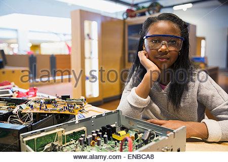 Portrait of confident girl assembling electronics circuit - Stock Photo