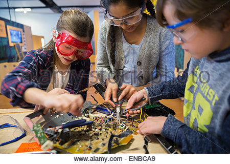 Students in goggles assembling electronic circuit science center - Stock Photo