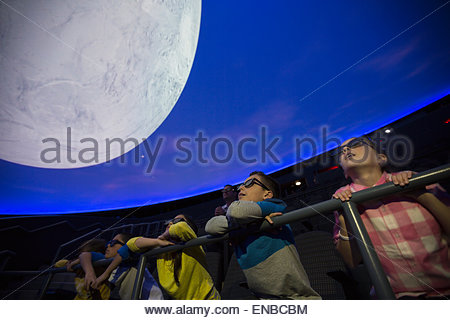 Curious students watching moon in planetarium show - Stock Photo