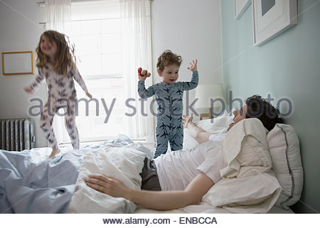 Father and children in pajamas playing in bed - Stock Photo