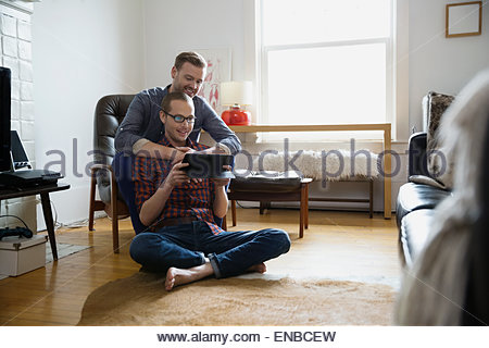 Homosexual couple using digital tablet in living room - Stock Photo