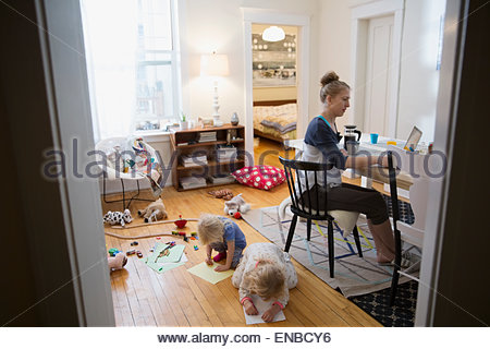 Mother working from home while children play - Stock Photo