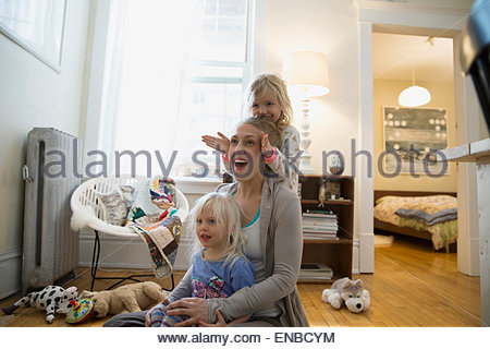 Mother and daughters on living room floor - Stock Photo
