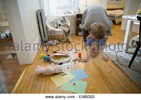 Playful mother and daughter in living room - Stock Photo