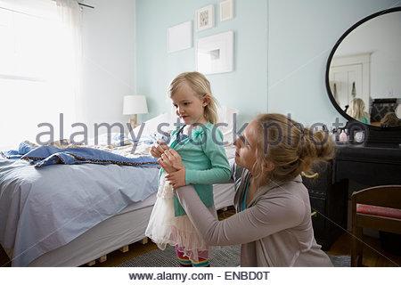 Mother dressing daughter in bedroom - Stock Photo