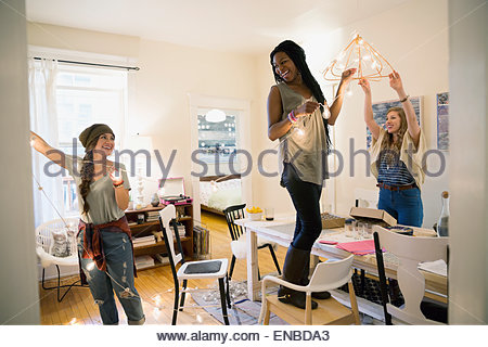 Friends hanging string lights in dining room - Stock Photo