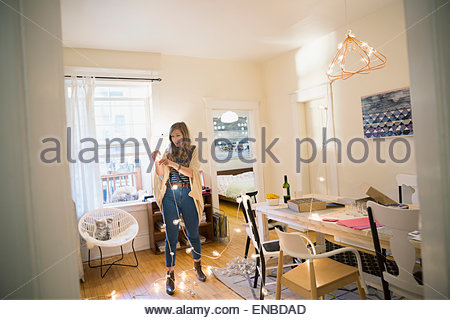 Woman hanging string lights in dining room - Stock Photo